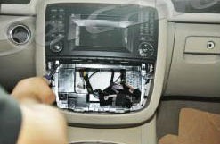 Remove two screws holding the stereo in the dashboard frame with a screwdriver