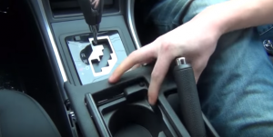 Remove the panel on downside of the e-brake. Please make sure your e-brake is up