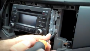 There are four screws holding the radio on the dashboard. Use a screwdriver to remove them