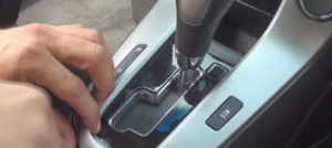 Pry the shifter surround panel. On manual transmission vehicles, unclip and reposition the shifter. Then remove the panel