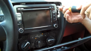 Use a screwdriver to remove the four screws that are holding the original car radio